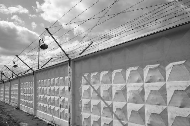 Linterna y alambre de púas con electricidad conectada - fotografía en blanco y negro.