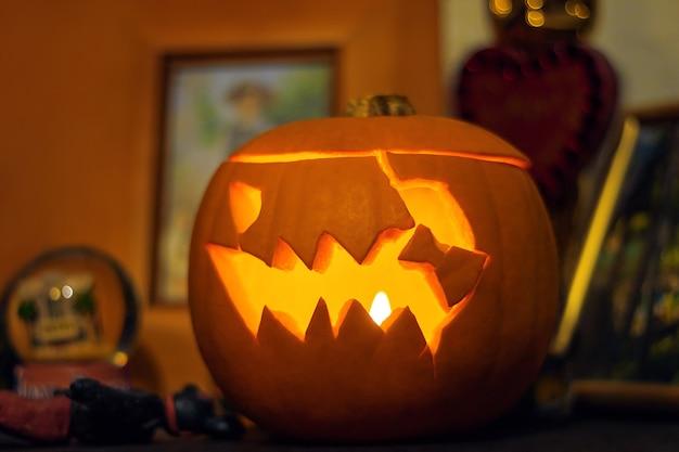 Linterna de calabaza de halloween tallada. cara de calabaza aterradora con una vela encendida dentro