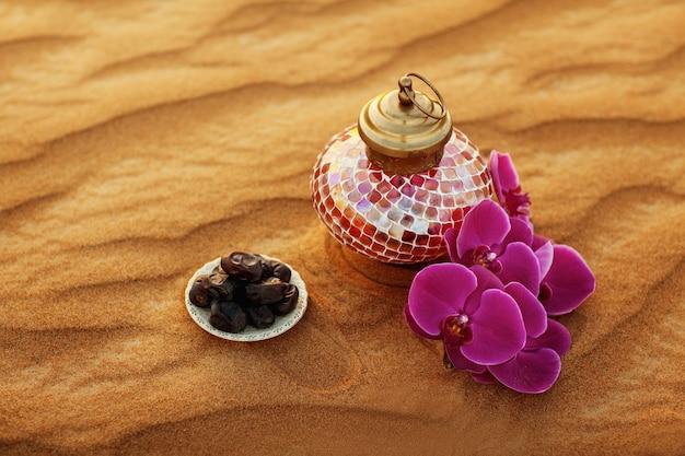 Linterna, flor y fechas en el desierto en una hermosa puesta de sol, que simboliza el ramadán