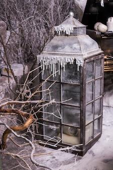 Linterna grande en invernadero. shabby style.winter vacaciones decoración al aire libre, linterna vintage. decoraciones navideñas con escena de invierno cubierto de nieve