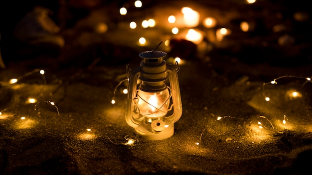 Linterna con guirnalda ardiente en la arena