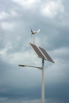 Linterna con una linterna y paneles solares instalados en el cielo azul