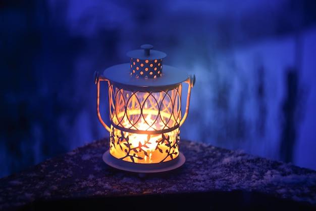 Linterna de navidad decorativa con vela encendida colgando de la rama de abeto cubierto de nieve en un parque de invierno. tarjeta festiva de año nuevo, cartel, diseño de postal.