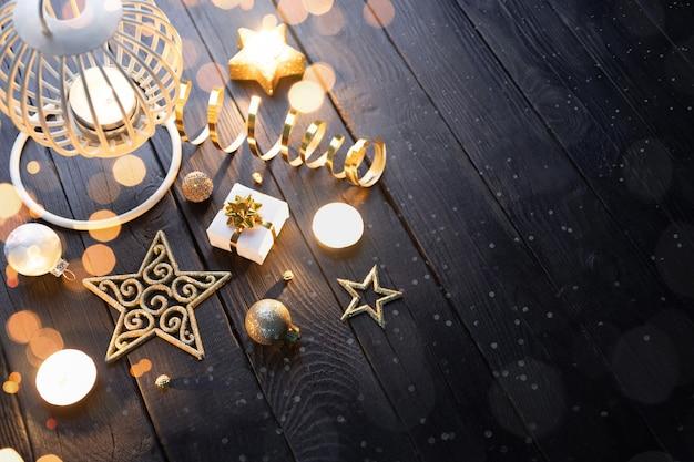Linterna de navidad con velas y adornos sobre una mesa de madera oscura.