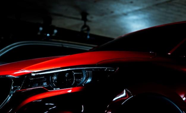 Linterna del primer del coche de lujo rojo brillante suv estacionado en un estacionamiento subterráneo del centro comercial