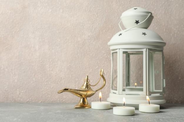 Linterna de ramadán con lámpara y velas en la mesa gris sobre fondo claro