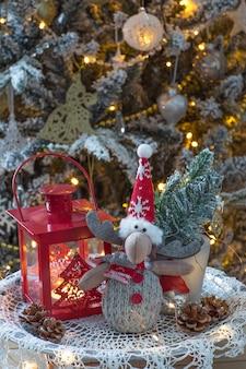 Linterna, ramas de abeto y alces de juguete debajo de un árbol de navidad