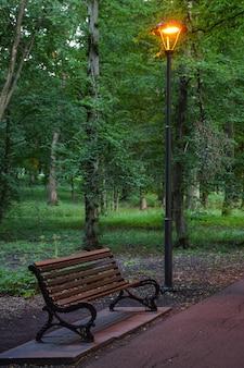Linterna resplandeciente en un parque de noche de verano, debajo de un banco para relajarse y una pasarela