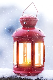 Linterna de la vela de navidad en un fondo cubierto de nieve fuera, concepto de navidad
