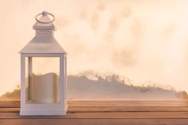Linterna con vela en tablero de madera cerca de montón de nieve a través de la ventana