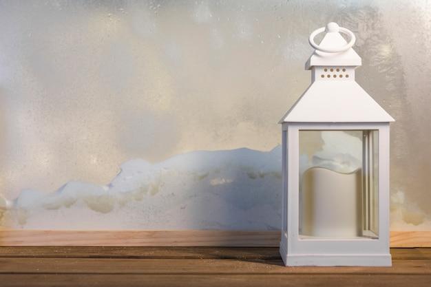 Linterna con vela en el tablero de madera cerca del montón de nieve a través de la ventana