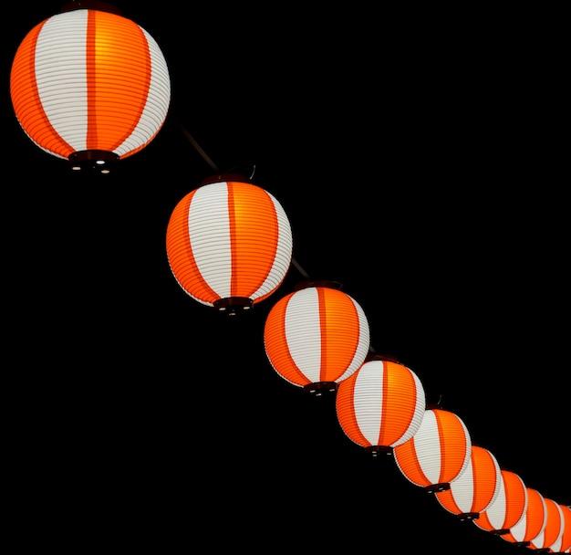 Las linternas chinas japonesas asiáticas rojo-blancas de papel brillan en el cielo oscuro.