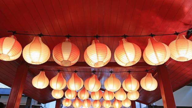 Linternas japonesas asiáticas rojo-blancas de papel en fila que brillan intensamente.