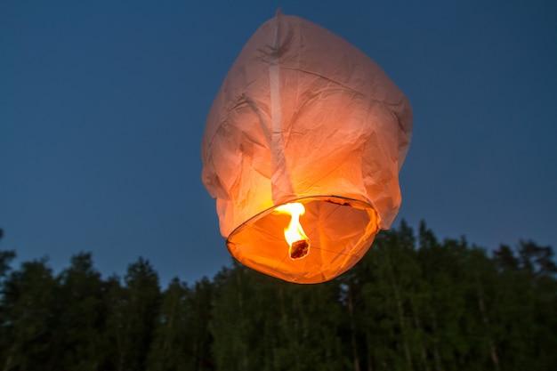 Linternas voladoras chinas, volando sobre el lago en la oscuridad