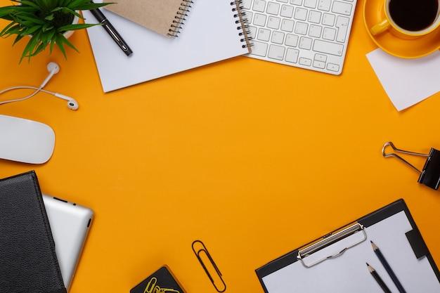 Lío de fondo amarillo en su teclado de escritorio, ratón, taza de café