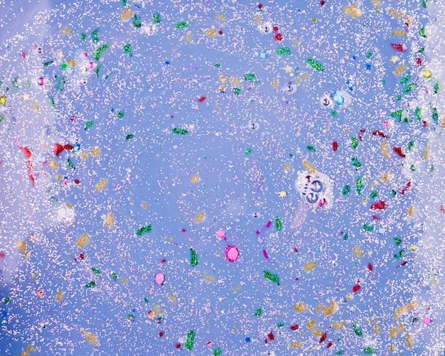 Líquido de aguamarina con burbujas y trozos de colores