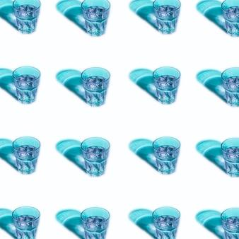 Líquido azul en vasos con sombra sobre fondo blanco