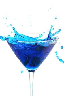 Líquido azul vertiendo en vidrio