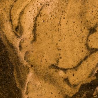 Líquido marrón con espuma profunda.
