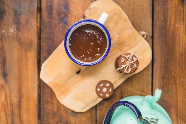 Líquido marrón en taza cerca de galletas y hervidor