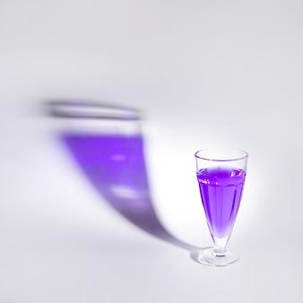 Líquido púrpura en el único vaso con sombra sobre fondo blanco
