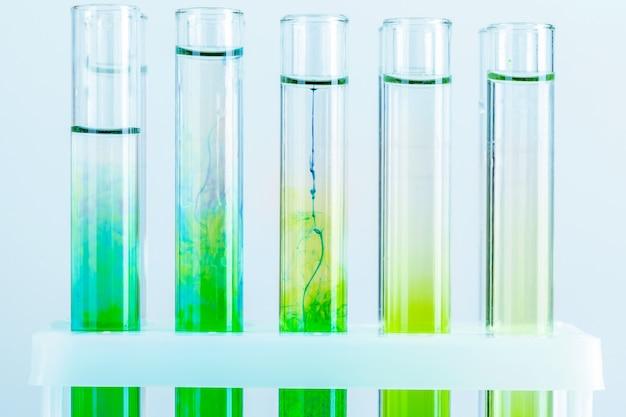 Líquidos verdes en tubos de ensayo en laboratorio químico de cerca