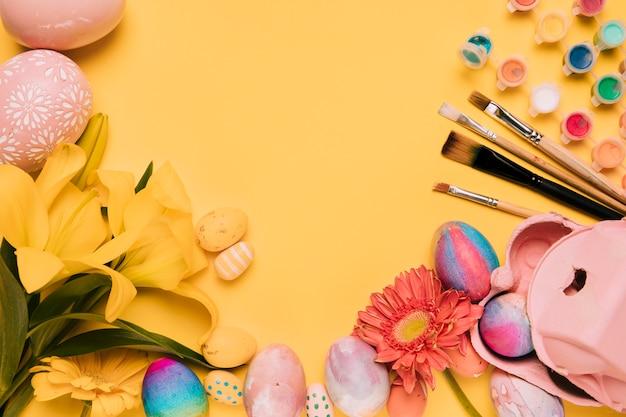 Lirio; flor de gerbera; cepillo de pintura; pintura de acuarela; con huevos de pascua sobre fondo amarillo