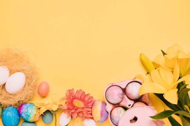Lirio; flor de gerbera con huevos de pascua sobre fondo amarillo