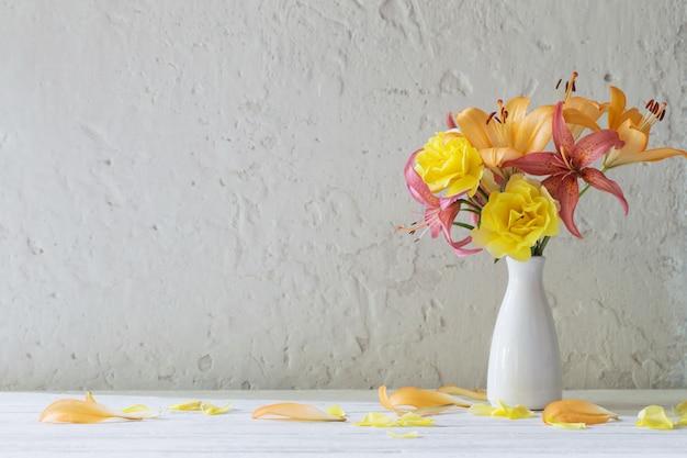 Lirios y rosas en jarrón blanco sobre fondo blanco.