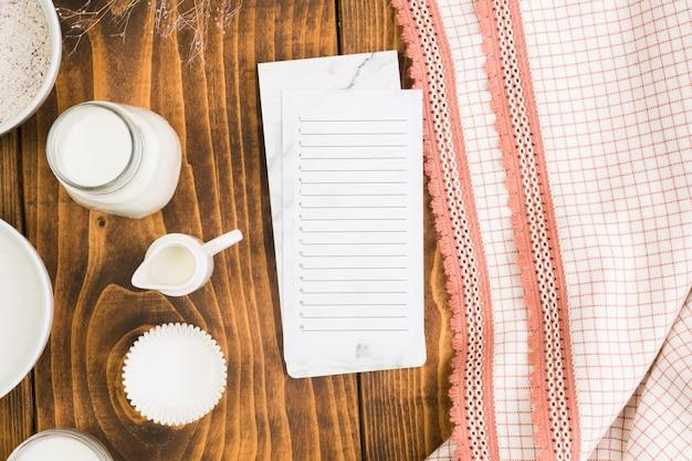 Lista en blanco en el bloc de notas con el tarro de leche y el molde para pastel sobre el escritorio de madera cerca del mantel