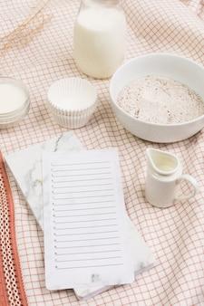 Lista en blanco en el diario con harina; tarro de leche y moldes sobre fondo de tela.