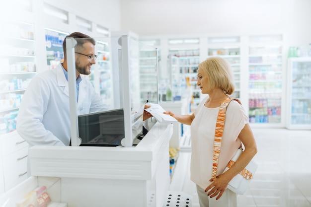 Lista de chequeo. químico encantado de pie en su lugar de trabajo mientras consulta a su visitante