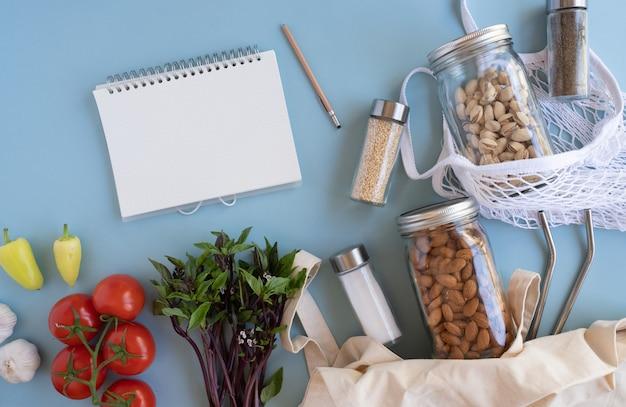 Lista y cuaderno para un estilo de vida sin desperdicio. bolsa de red de algodón con verduras frescas y tarro de cristal sostenible sobre fondo azul plano. libre de plástico para la compra y entrega de productos alimenticios.