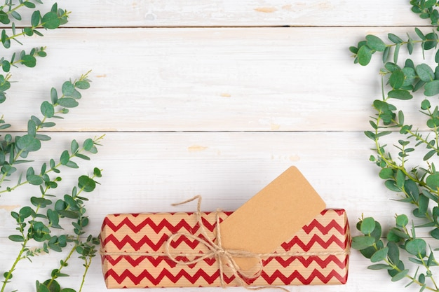 Lista de deseos de navidad vacía con pequeño regalo sobre fondo de madera