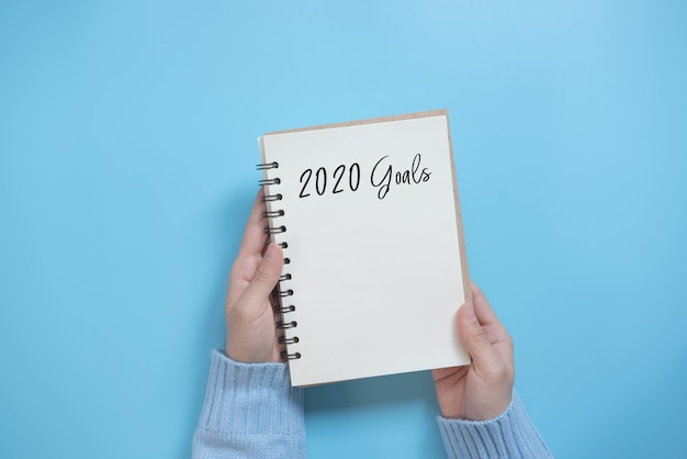 Lista de objetivos de año nuevo 2020 con cuaderno sobre fondo azul, estilo plano. concepto de planificación.
