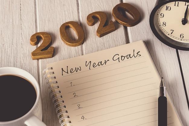 Lista de objetivos de año nuevo escrita en el cuaderno con reloj despertador, bolígrafo, café