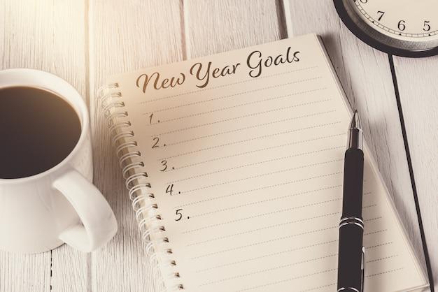 Lista de objetivos de año nuevo escrita en un cuaderno con reloj despertador, bolígrafo y café
