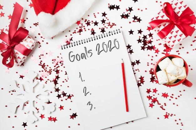 Lista de objetivos nuevo año 2020. decoración navideña. planificación y lista de tareas con decoración roja de vacaciones.
