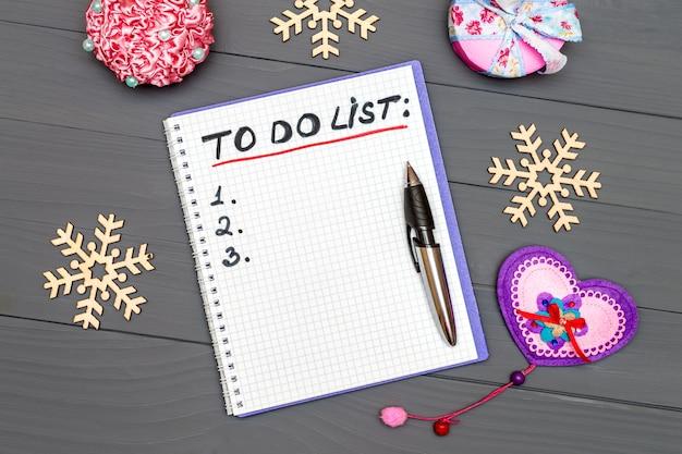 Lista de páginas de papel con pan y adornos de año nuevo en la superficie de la mesa de escritorio de madera