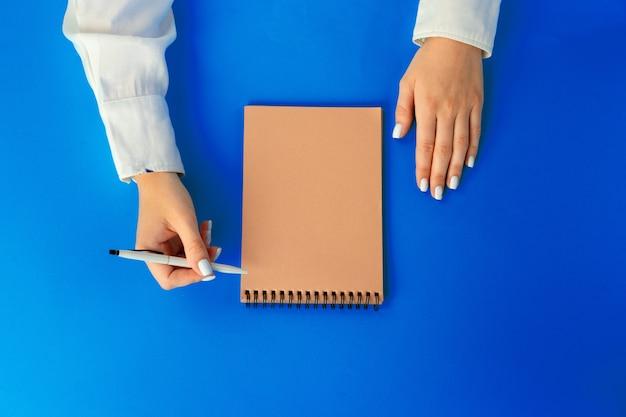 Lista de quehaceres. vista superior de manos femeninas escribiendo en el cuaderno