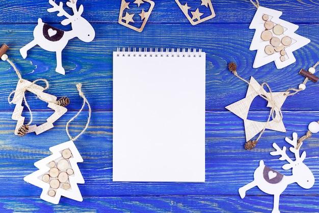 Lista de resolución de año nuevo con decoraciones de navidad sobre fondo de madera azul