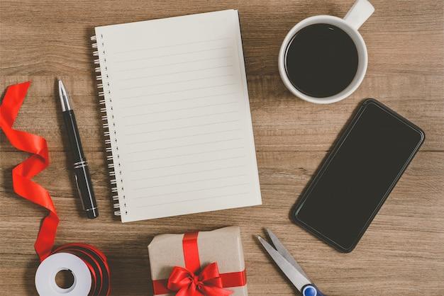 Lista de resoluciones de año nuevo escrita en el cuaderno con caja de regalo y teléfono inteligente, bolígrafo, café