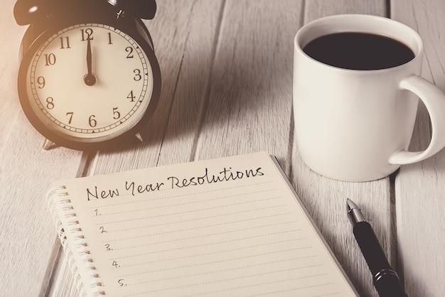 Lista de resoluciones de año nuevo escrita en el cuaderno con despertador, bolígrafo, café