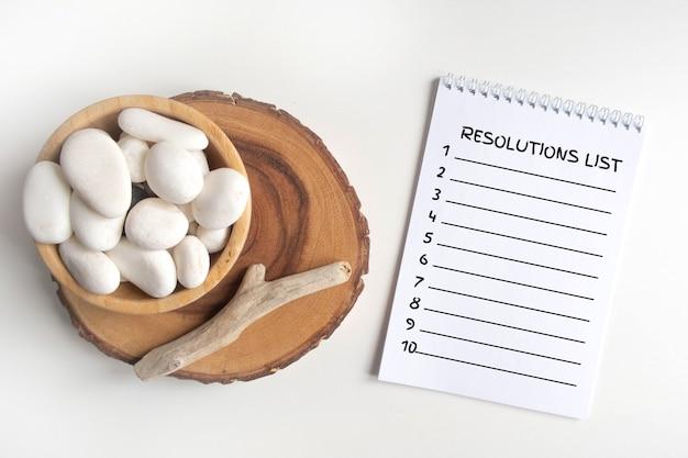 Lista de resoluciones con un tazón de guijarros blancos