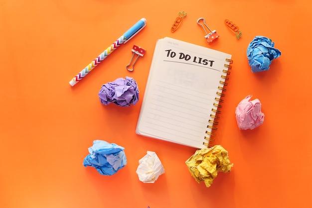 Lista de tareas en el cuaderno con proveedores de oficina en naranja