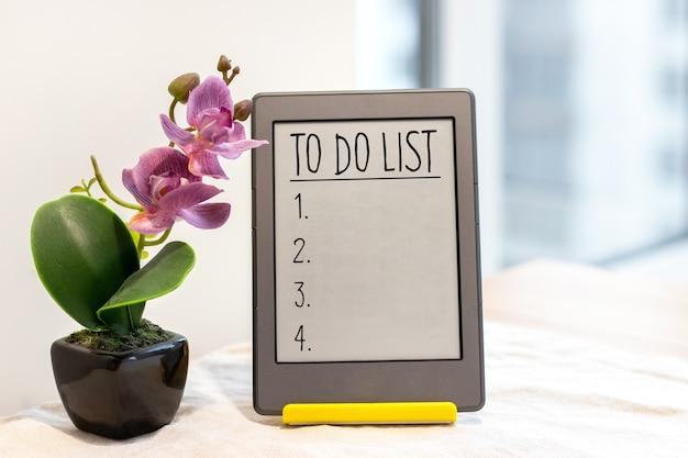 Lista de tareas en tableta junto a una orquídea rosa artificial
