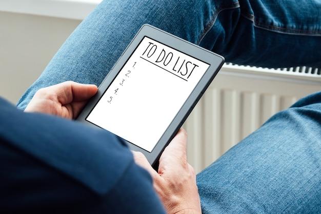 Lista de tareas en tableta en manos del hombre