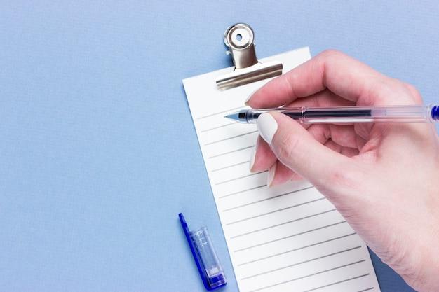 Lista de verificación comercial importante, planificación de recordatorio de compras o lista de tareas prioritarias del proyecto sobre fondo azul con espacio de copia. pluma en manos femeninas
