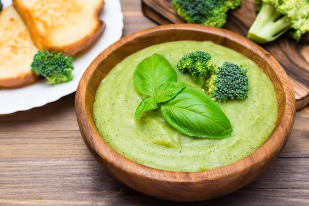Listo para comer sopa de puré de brócoli caliente caliente con trozos de brócoli y hojas de albahaca en un plato de madera sobre una mesa de madera.