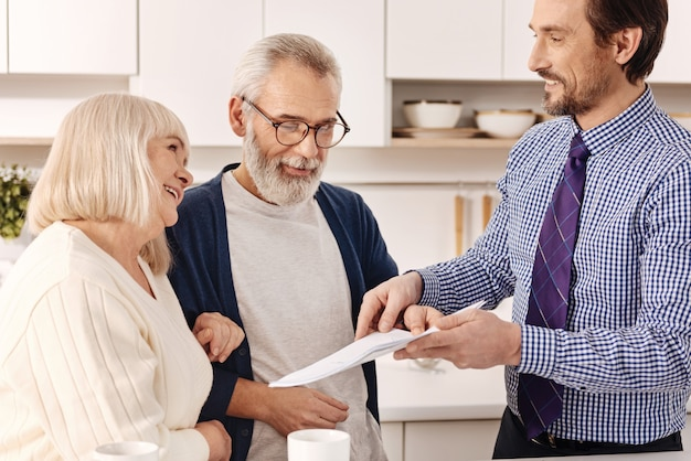 Listo para contrato financiero. amables, encantadores, optimistas, propietarios de parejas mayores que se reúnen con un agente inmobiliario y lo consultan mientras eligen la variante para la inversión
